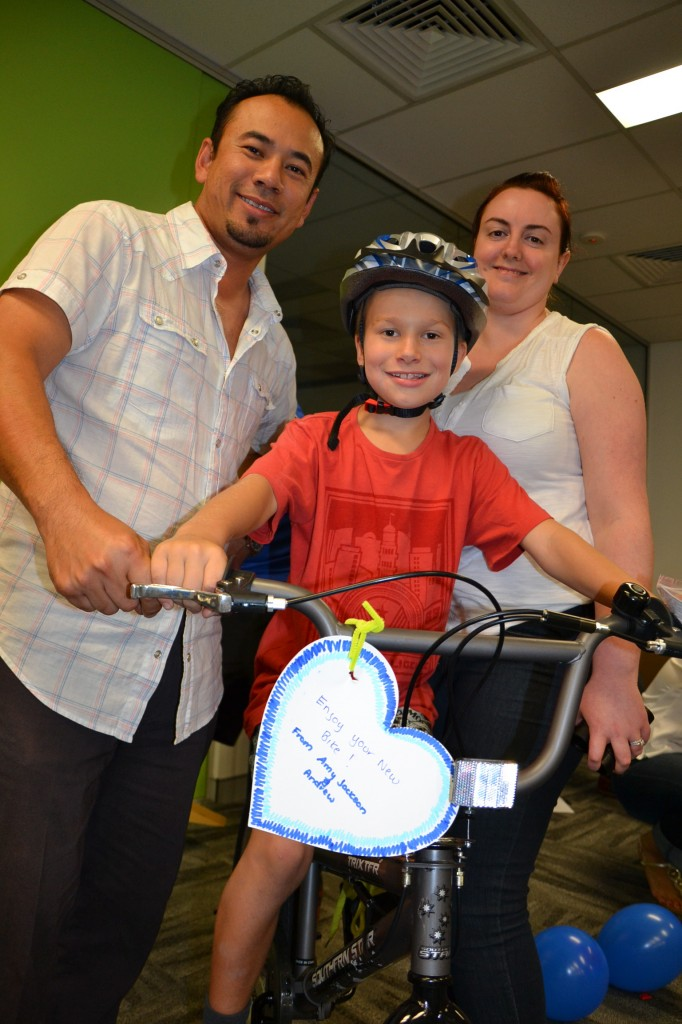 Build a bike for kids happily sitting on bike built by staff that is rewarding for all!