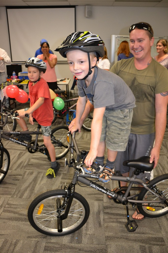 Independent Kids Happy and Standing Tall next to dad - thanks to the corpporate team building Build-a Kids-bike at Medtronic in Ryde.